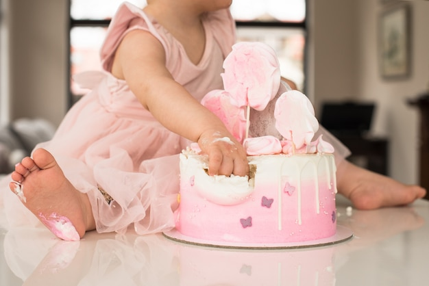 Celebration of the first birthday of the girl, ruined sponge cake, broken marshmallow, baby hands and lags. permissiveness, disobedience, eating with hands Premium Photo