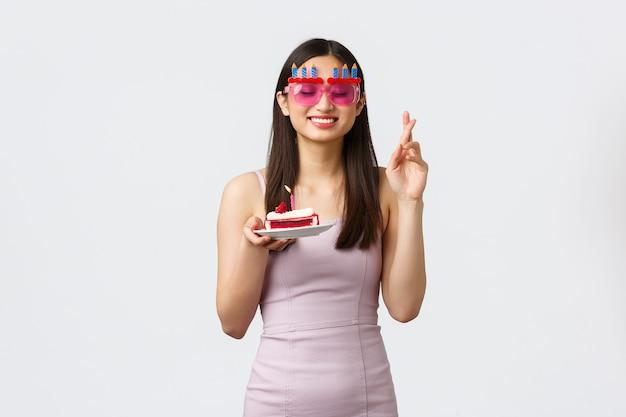 Концепция празднования, вечеринки и праздников. мечтательная обнадеживающая азиатская именинница в платье, скрестив пальцы, желает закрытых глаз и улыбки Premium Фотографии