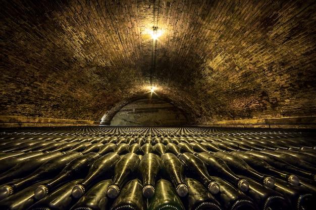 Un tunnel della cantina con bottiglie di vetro Foto Gratuite