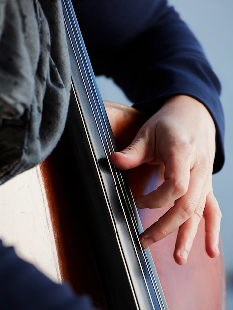 Cellist player hands. violoncellist playing cello on background of field. musical art, concept passion in music. classical music professional cello player solo perform Free Photo