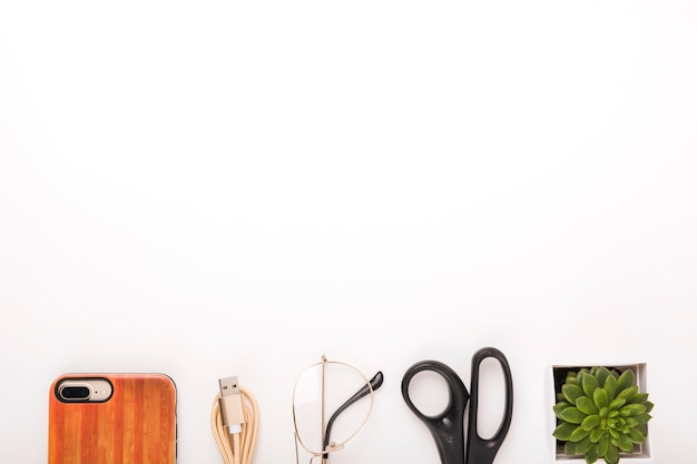 Cellphone; usb cable; spectacles; scissors and potted plant at the bottom of white background Free Photo