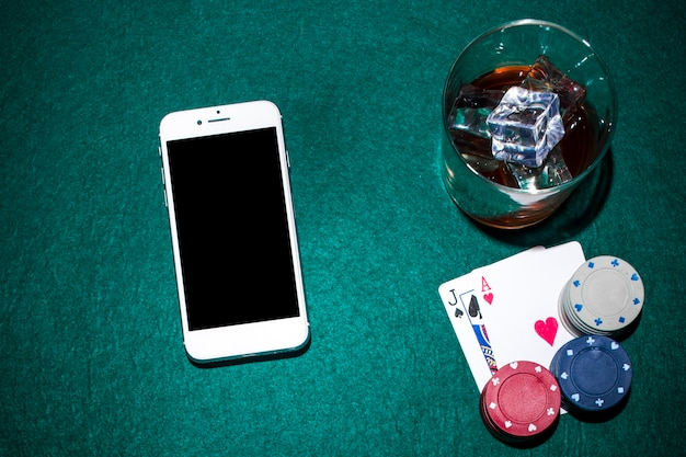 Cellphone and whisky glass with jack of spade and heart ace cards on green poker table Free Photo