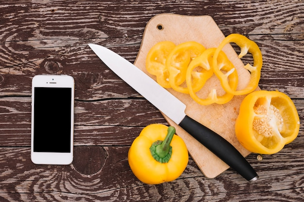 Cellphone with yellow bell pepper and knife on wooden desk Free Photo