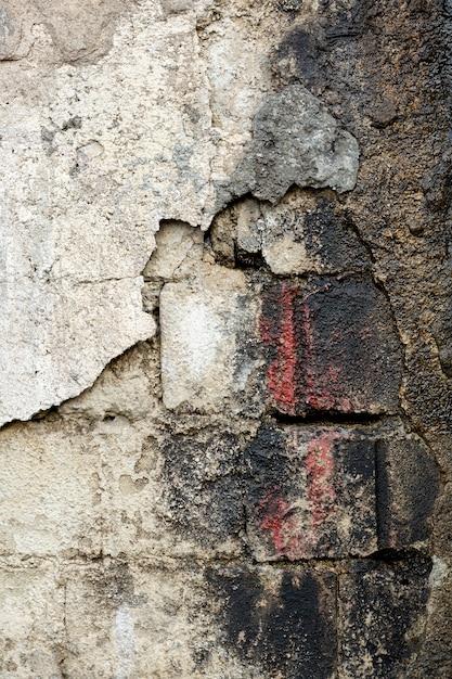 Muro di cemento con mattoni e vernice sporchi a vista Foto Gratuite