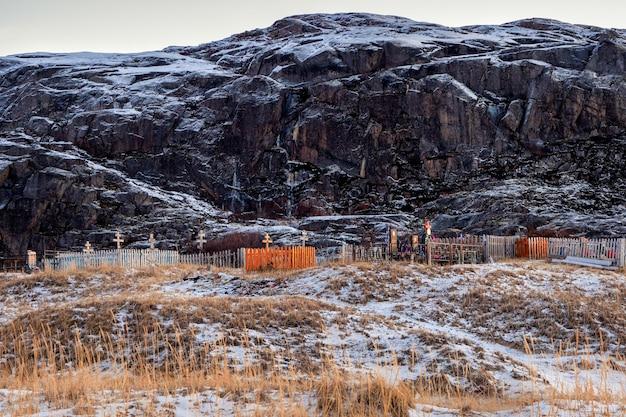 Teriberka의 북극 해안 언덕 배경에 묘지 프리미엄 사진