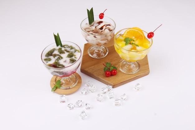 白いテーブルの上のグラスにおいしい甘いオランウータンジュース、ココナッツジュース、およびcendolインドネシアの人気のある飲み物 Premium写真