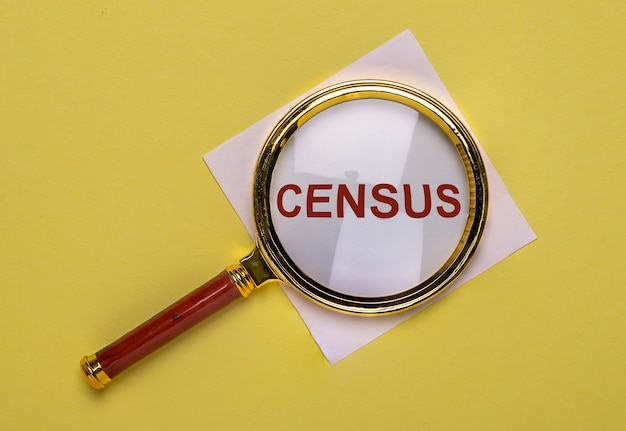 Census word through magnifier over yellow background. Premium Photo