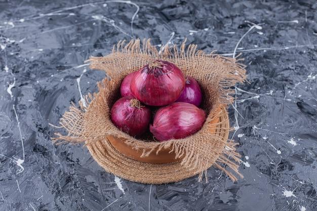 青い表面に新鮮な赤玉ねぎのセラミックボウル 無料写真