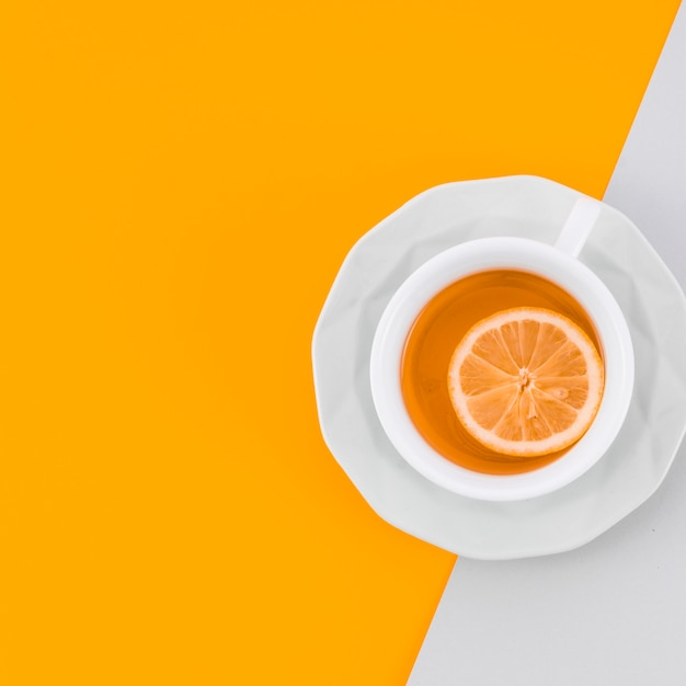 Ceramic cup of ginger tea with lemon on yellow and white background Free Photo