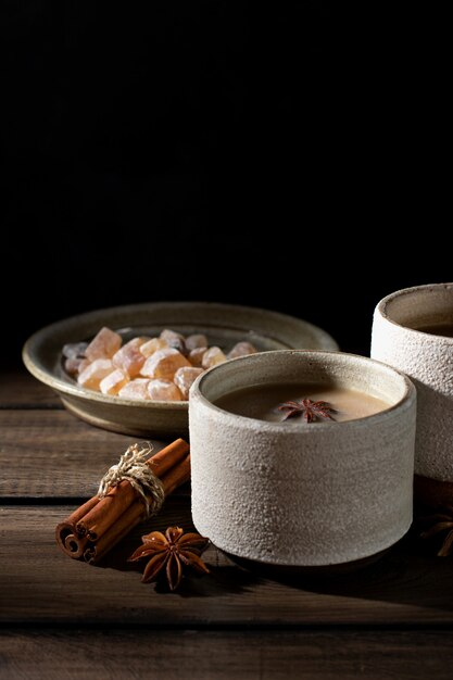 Керамическая чашка чая масала со специями и сахаром на деревянном столе Premium Фотографии