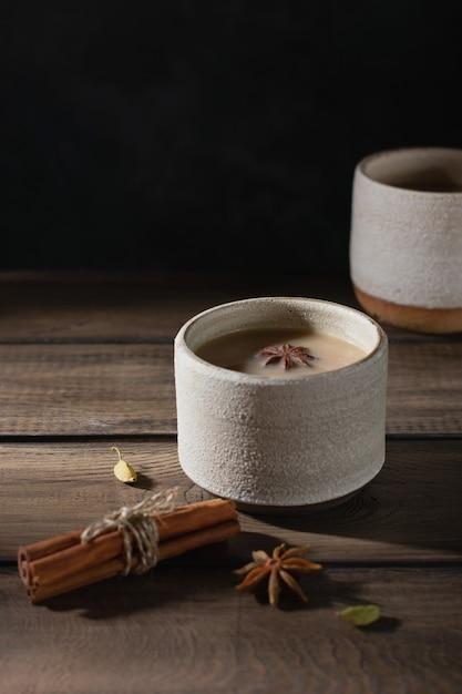 Керамическая чашка чая масала со специями на деревянном столе Premium Фотографии