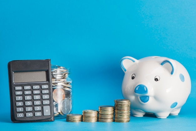 Ceramic piggybank; calculator; glass jar and stack of coins against blue background Free Photo