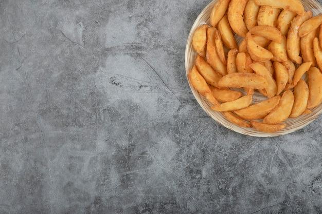 Ceramic plate of tasty fried potato wedges on stone background. Free Photo