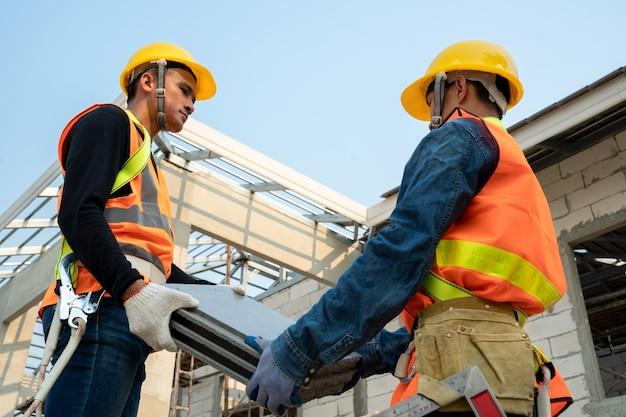 屋根葺き職人によるセラミック瓦の設置、建設中の住宅のコンセプト。 Premium写真