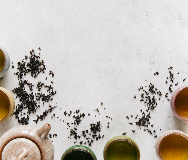 Ceramic teapot with herbal teacup on concrete backdrop Free Photo