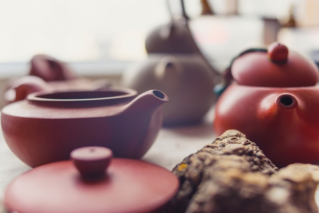 Ceramic teapots stand on a window in a cafe Premium Photo