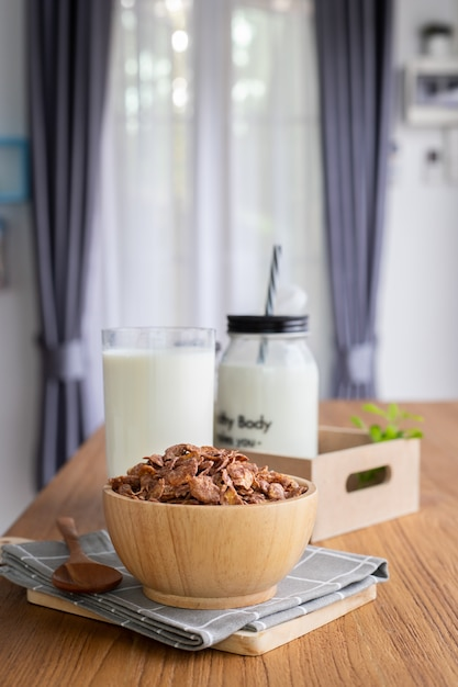Cereal breakfast with glass of milk, bottle of milk on wood table in living room. Premium Photo