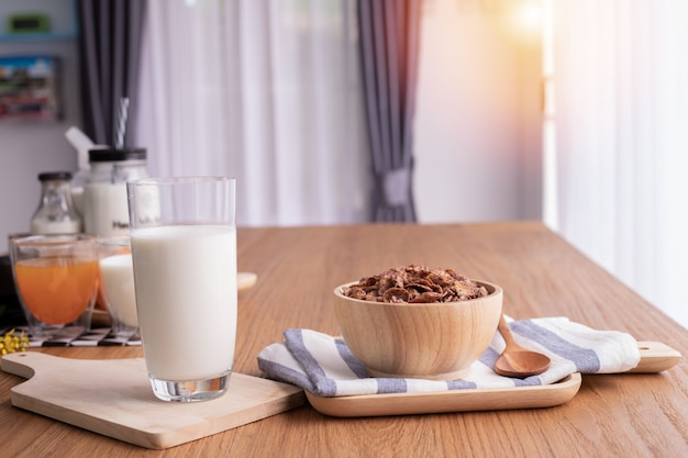 Cereal breakfast with glass of milk on wood table in living room. top table. Premium Photo