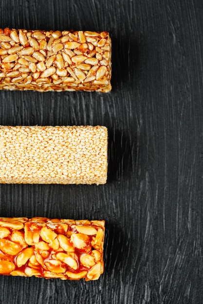 Cereal granola bar with peanuts, sesame and sunflower seeds on a cutting board on a dark stone table. view from above. three assorted bars Premium Photo