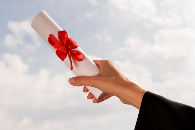 Certificate with ribbon and bow held in hand Free Photo