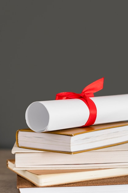 Certificate with ribbon front view and books Premium Photo