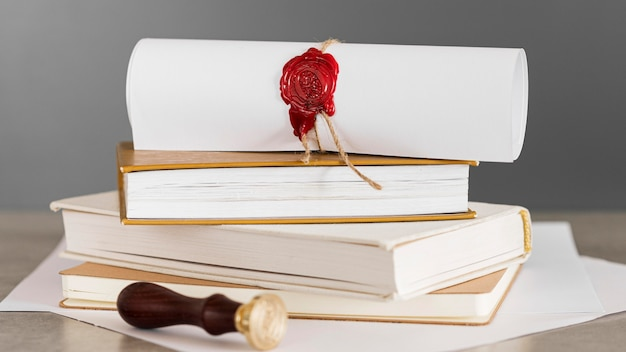 Certificate with wax seal on a pile of books front view Premium Photo