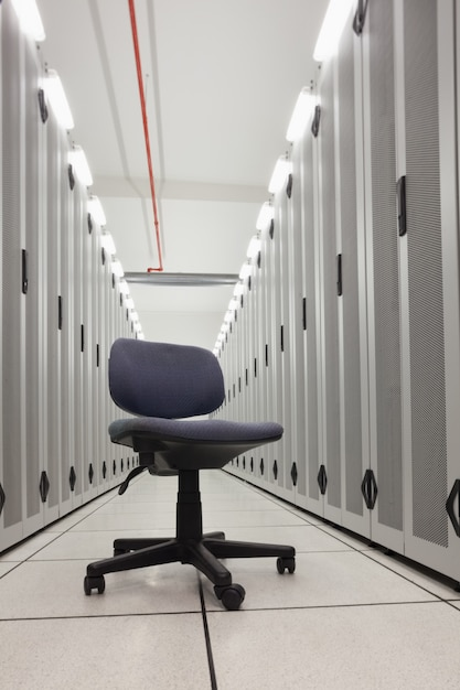 Chair in empty row of servers Premium Photo