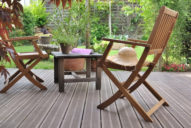 Chairs to relaxe on wooden terrace  in a garden Premium Photo