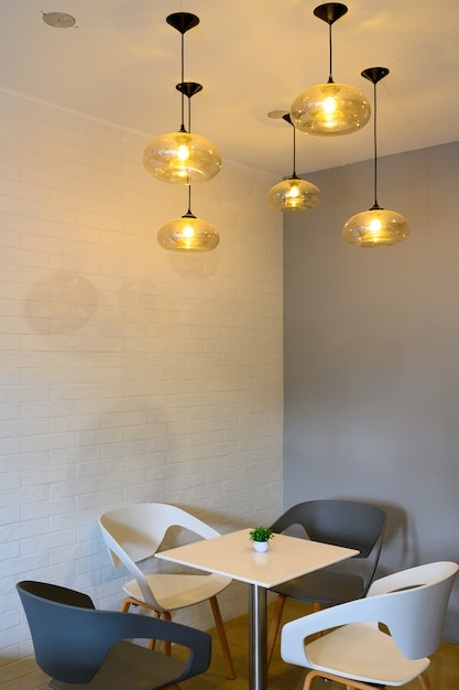 Chairs table and ceiling lamp in restaurant Premium Photo