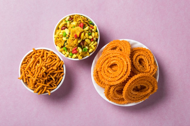 Chakli、chakaliまたはmurukku and besan(gram flour)sev and chivada on pink Premium写真