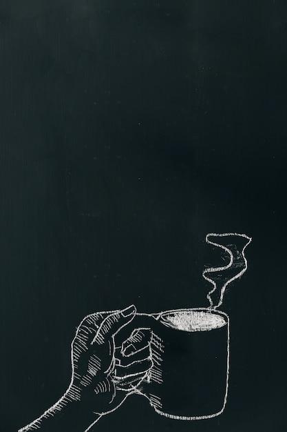 Мел руки, вытянув руку с чашкой кофе с паром на черной доске Premium Фотографии