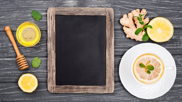 Chalkboard beside cup with lemon tea and honey Free Photo