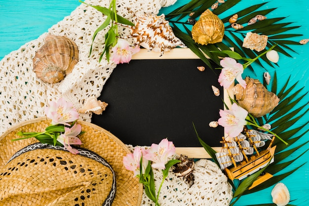 Chalkboard between plant leaves with flowers near seashells and hat Free Photo