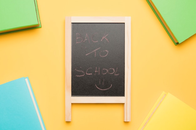 Chalkboard surrounded by books in colorful covers Free Photo