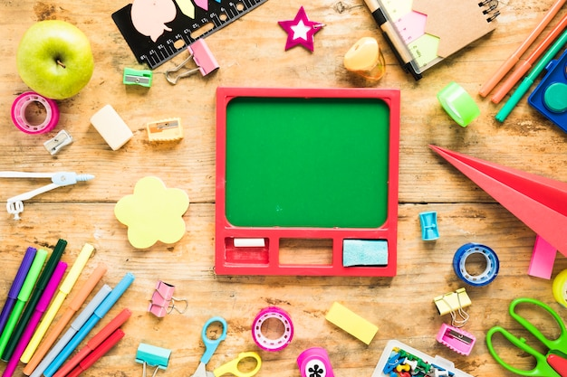 Chalkboard surrounded by stationery objects Free Photo