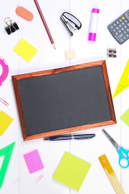 Chalkboard surrounded by stationery on white wooden table. copy the space. Premium Photo