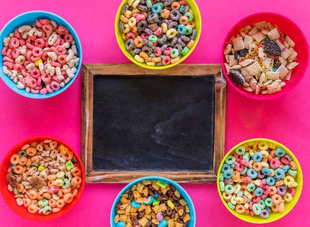 Chalkboard with bowls of cereals on table Free Photo
