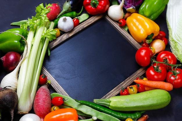 어두운 배경에 다른 다채로운 건강 야채와 함께 칠판 무료 사진