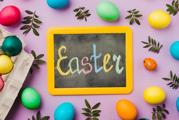 Chalkboard with Easter title between set of colored eggs and leaves near container Free Photo