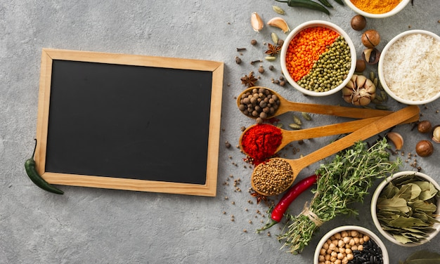 Chalkboard with spices and herbs top view with rice, various beans Premium Photo