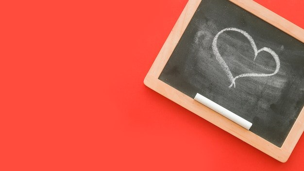 Chalkdrawn heart shape on slate over red background Free Photo