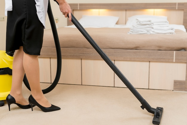 Chambermaid cleaning hotel room Free Photo