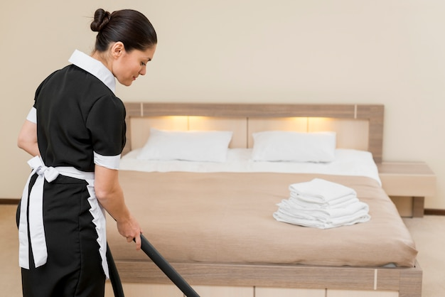 Chambermaid cleaning hotel room Premium Photo