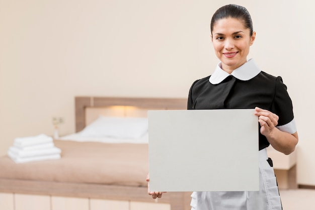 Chambermaid in hotel room with laptop Free Photo