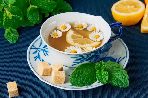 暗いランチョンマットの背景にカップとレモンスライス、ブラウンシュガーキューブ、緑の葉の側面図でカモミールティー 無料写真