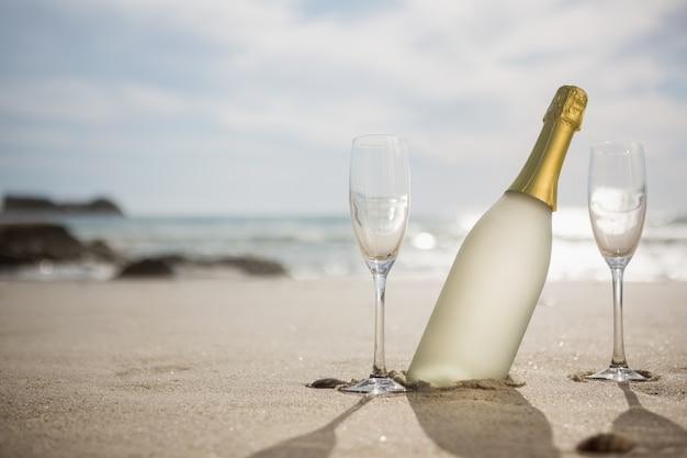 シャンパンボトルや砂の上の2つのメガネ 無料写真