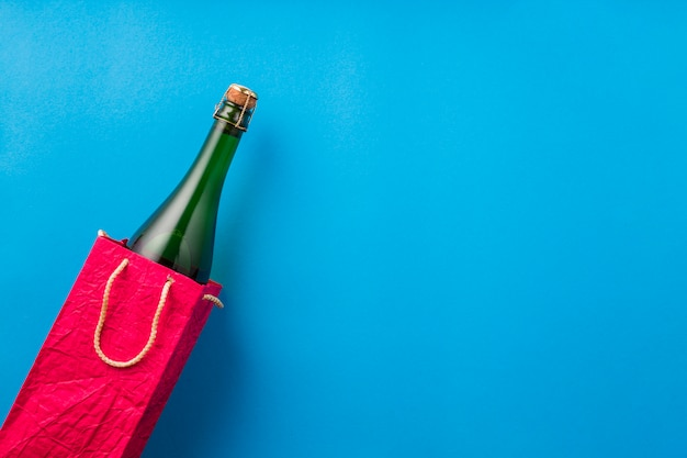 Champagne bottle in bright red paper bag on blue surface Free Photo