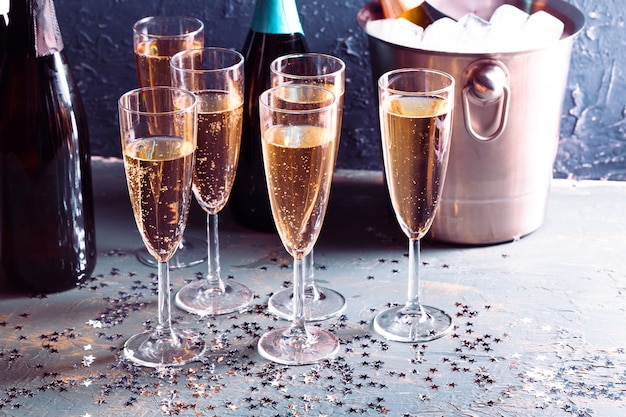 Champagne bottle in bucket with ice and glasses of champagne Premium Photo