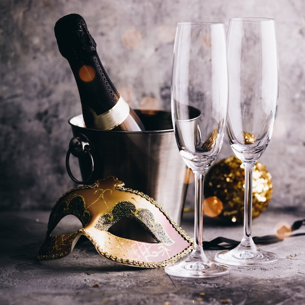 Champagne bottle in bucket with ice, glasses and christmas decorations Premium Photo