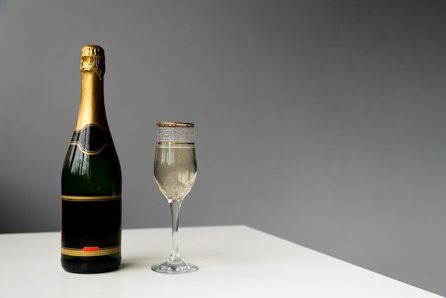 Champagne bottle and champagne glass on white table Free Photo